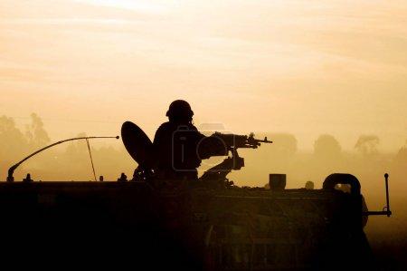 Foto de Silueta de un soldado del ejército prepara su tanque y armas al atardecer - Imagen libre de derechos