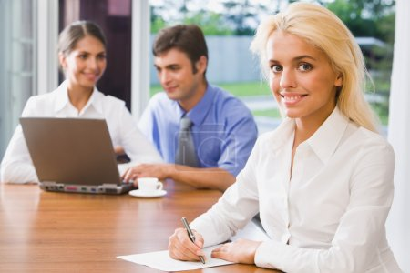 Photo for Pretty smiling woman on a background of her the coworkers in the office - Royalty Free Image