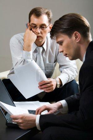 Photo pour Portrait de deux homme d'affaires concentré assis sur les chaises munies de documents dans leurs mains et travaillant sur l'ordinateur portable placé sur la table avec des papiers sur elle - image libre de droit