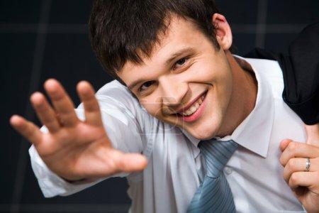 Photo pour Isolé sur le portrait noir d'un bel homme d'affaires souriant regardant la caméra agitant la main - image libre de droit