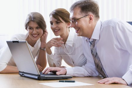 Group of three business looking at monitor
