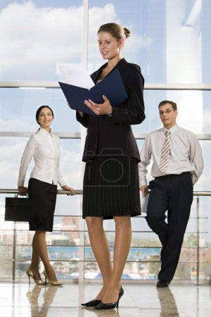 Photo pour Souriant de lecture des documents caucasien de femme d'affaires dans l'immeuble de bureaux modernes et deux hommes d'affaires sur le fond - image libre de droit