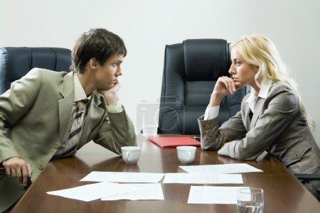 Photo pour Deux affaires devant l'autre regardant fixement l'un l'autre assis à la table avec des tasses, un verre d'eau, un étui en papier et des documents jetés dessus et des chaises noires vides autour - image libre de droit