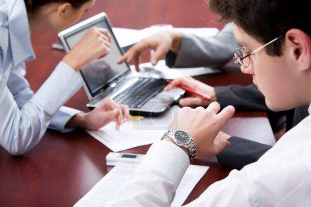 Photo pour Homme d'affaires regardant sa montre-bracelet dans un environnement de travail - image libre de droit