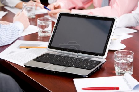 Image of laptop on workplace with associates talking on background