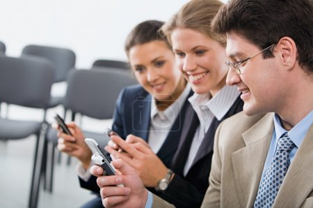 Photo for Portrait of young businesspeople exchanging an information on the mobile phones - Royalty Free Image