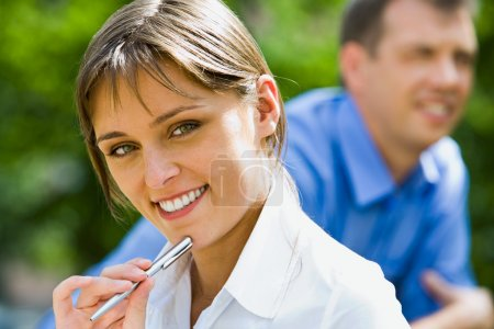 Photo for Portrait of young beautiful woman holding the pen on the background of business man - Royalty Free Image