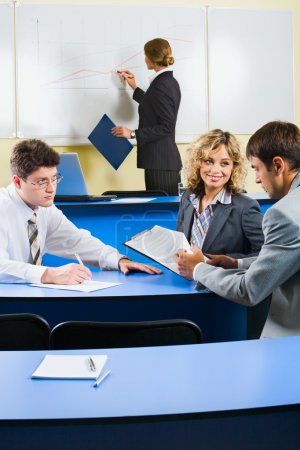 Photo for Group of sitting at the blue table and discussing business questions in the class room - Royalty Free Image