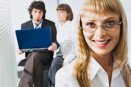 Photo for Portrait of smiling smart specialist with glasses on the background of two businesspeople - Royalty Free Image