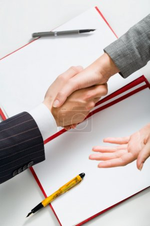 Photo for Successful sale: business handshake with paper, folder, two pens in the background - Royalty Free Image