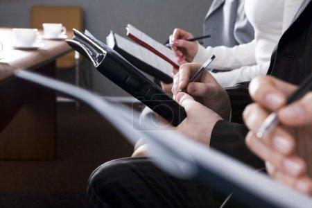Foto de Fila de manos rellenando un formulario - Imagen libre de derechos