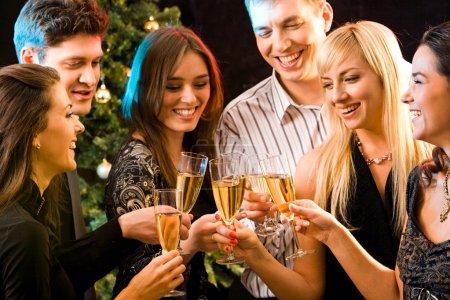 Foto de Imagen de varios atractivos amigos haciendo un tintineo de tudeles champagne - Imagen libre de derechos