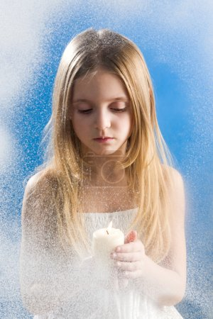Photo pour Photo de fille paisible avec une bougie debout derrière une fenêtre enneigée - image libre de droit