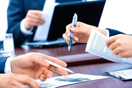 Photo pour Gros plan des mains de l 'entreprise tenant stylos et documents lors de la réunion - image libre de droit