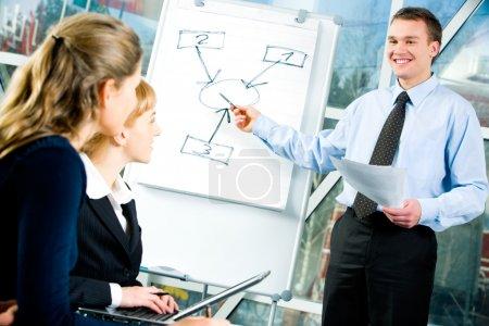 Photo pour Image de l'homme confiant expliquant sa stratégie d'entreprise pointant vers le conseil d'administration à ses collègues - image libre de droit