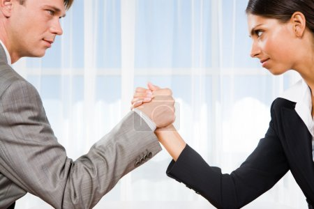 Photo for Man and woman in arm wrestling gesture on working table during meeting - Royalty Free Image
