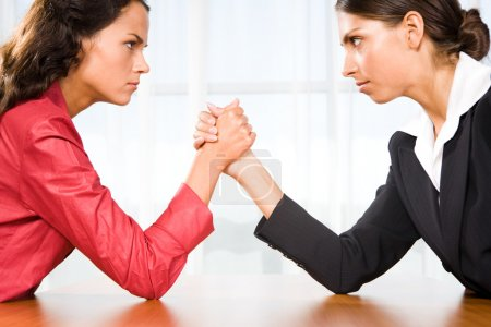 Photo for Profile of two women in struggle while their arms being wrestled - Royalty Free Image