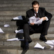 Anxious businessman sitting on stairs while readin...