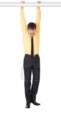 Photo pour Photo d'un homme d'affaires effrayé pendu tout en tenant par barre horizontale sur fond blanc - image libre de droit