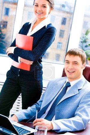 Foto de Retrato de la mujer de negocios de pie y el hombre sentado en la mesa cerca - Imagen libre de derechos