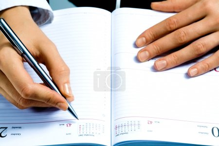 Photo for Image of writing instrument in human hands over notepad - Royalty Free Image