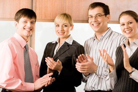 Photo pour Portrait de quatre affaires souriant et applaudissant au bureau - image libre de droit