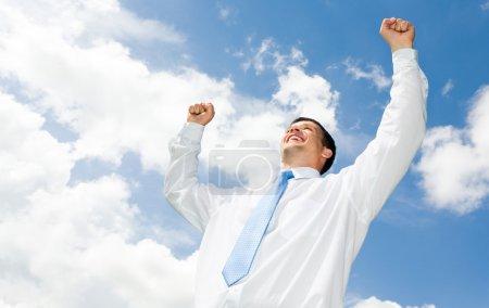 Photo pour Portrait d'homme d'affaires heureux, levant ses mains avec un ciel nuageux au-dessus de lui - image libre de droit