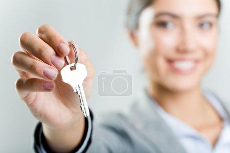 Happy woman's hand holding new key