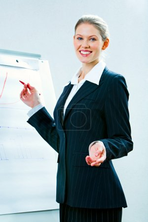 Photo for Portrait of confident teacher explaining a new lecture standing with whiteboard near by - Royalty Free Image