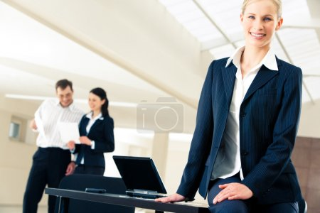 Photo for Portrait of elegant business lady at her workplace on the background of working partners - Royalty Free Image