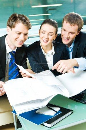 Photo for Vertical image of three sitting in the office and discussing business documents - Royalty Free Image