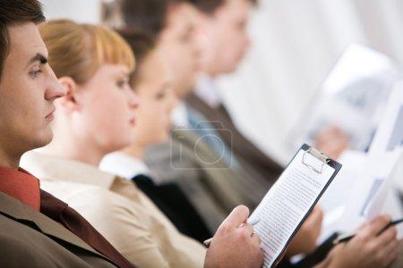 Photo pour Profil de l'homme grave, prendre des notes sur le document au cours du séminaire - image libre de droit