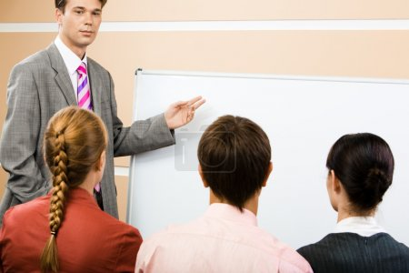 Photo for Image of serious businessman pointing at whiteboard with three partners listening to him - Royalty Free Image