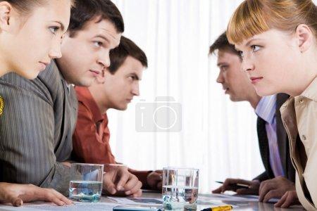Photo pour Profils d'employés sérieux assis en deux rangées et l'autre en regardant - image libre de droit