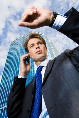 Photo pour Sous vue d'homme d'affaires, appeler au téléphone mobile et en regardant sa montre - image libre de droit