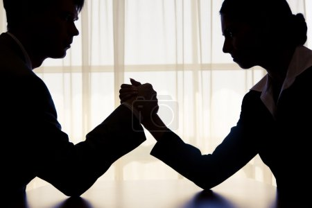 Photo for Silhouette of business competitors doing arm wrestling in office - Royalty Free Image