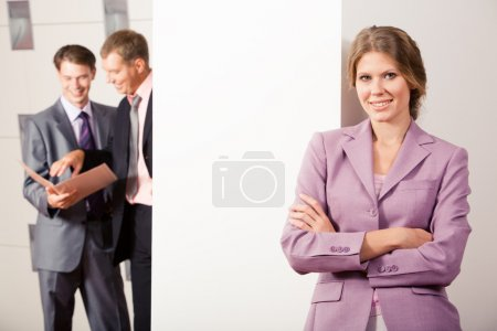 Photo for Portrait of charming lady in lilac jacket standing by the wall while two men speaking to each other behind it - Royalty Free Image