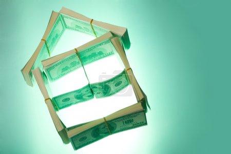 Photo pour Photo conceptuelle du modèle de petite maison fait nous dollars sur fond vert - image libre de droit