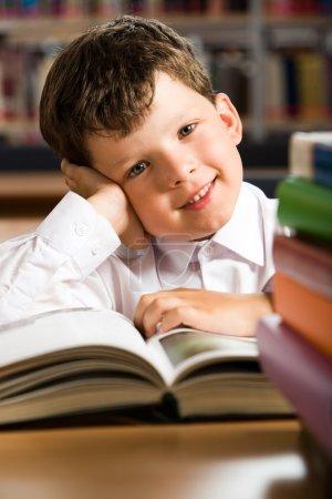 Photo pour Portrait d'un écolier souriant assis à la table avec des livres dessus - image libre de droit