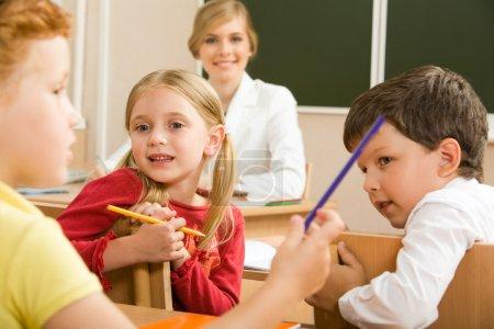 Photo pour Portrait des élèves assis dans la salle de classe et en parlant avec leur professeur derrière - image libre de droit