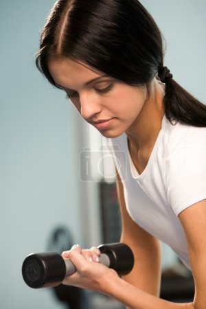Photo for Close-up of sporty girl lifting barbell in left hand in the sportive club - Royalty Free Image