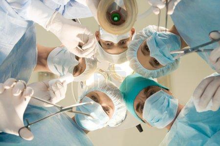Photo pour Ci-dessous vue des chirurgiens tenant des instruments médicaux dans les mains et regardant le patient - image libre de droit