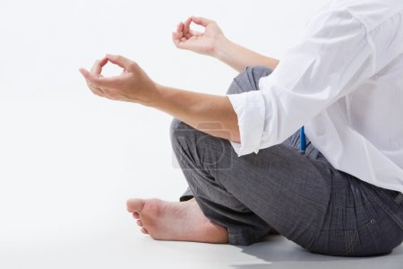 Photo of relaxed businessman meditating over white background