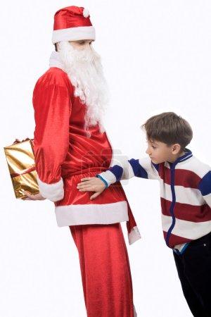 Photo pour Portrait du petit garçon à la recherche de cadeau de Noël caché par santa derrière son dos - image libre de droit