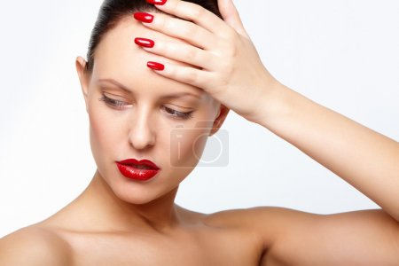 Photo for Posh woman with red lips and fingernails touching her forehead - Royalty Free Image