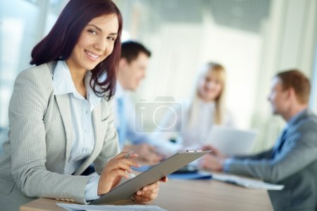 Photo for Young woman in foreground smiling at camera while her colleagues - Royalty Free Image