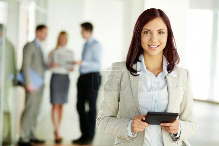 Photo pour Portrait d'une belle jeune fille tenant une tablette PC et en regardant la caméra - image libre de droit