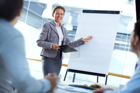 Photo for Tilt up shot of a business lady presenting her work to the associates - Royalty Free Image