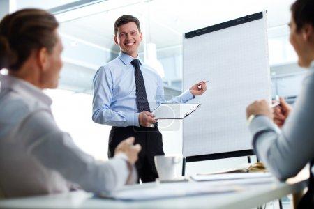 Photo pour Homme d'affaires joyeux discutant d'un nouveau projet d'entreprise avec les membres de son équipe - image libre de droit