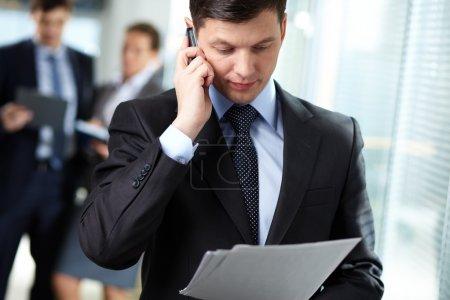 Photo pour Homme d'affaires répondant à un appel pendant que ses collègues discutent en arrière-plan - image libre de droit